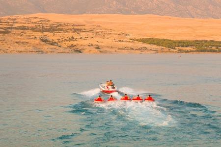 speedboat: Kids tube riding tawed by speedboat on Croatian coast. Summer sea fun and adventure. Exciting water sport.