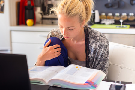 programmes: Adult woman in her casual home clothing working and studying remotly from her small flat in the morning. Home kitchen in the background. Great flexibility of web-based courses and study programmes. Stock Photo
