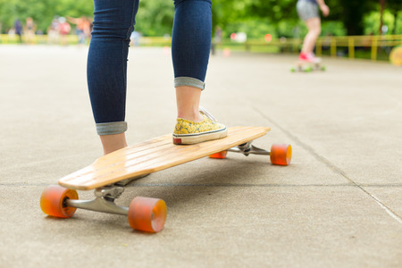 subculture: Teenage girl wearing blue jeans and sneakers practicing long board riding in skateboarding park. Active urban life. Urban subculture.