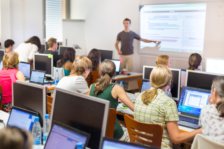 Workshop at university. Rear view of students sitting and listening in lecture hall doing practical exercises on their laptop computers.  Tutor explaining tasks on white board.