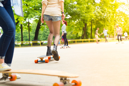 subculture: Teenagers practicing long board riding outdoors in skateboarding park. Active urban life. Urban subculture. Copy space.