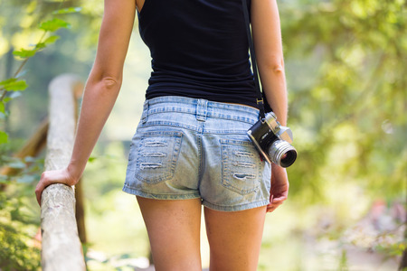 photo shooting: Rear body crop of a hipster girl wearing jeans shorts an sporty black sleeveless t-shirt, walking in nature, carrying vintage camera over her shoulder. Healthy active lifestyle.