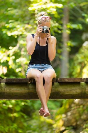 pantalones cortos: Hermosa descalzo niña caucásica rubia llevaba jeans cortocircuita un negro sin mangas de la camiseta deportiva, sentado en un puente de madera vintage, tomar fotos con la cámara retra.