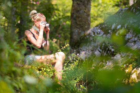 clearing: Beautiful barefooted blonde caucasian girl wearing jeans shorts an sporty black sleeveless t-shirt, sitting on a forest clearing, taking photos with retro camera.