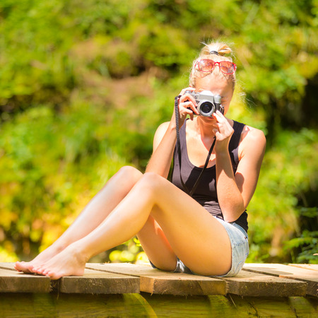 barefooted: Beautiful barefooted blonde caucasian girl wearing jeans shorts an sporty black sleeveless t-shirt, sitting on a vintage wooden bridge, taking photos with retro camera. Stock Photo