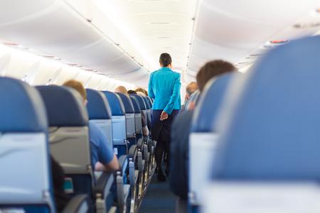 Interior de avión con los pasajeros de los asientos y azafata caminando por el pasillo.