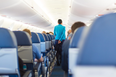 aisle: Interior of airplane with passengers on seats and stewardess walking the aisle.
