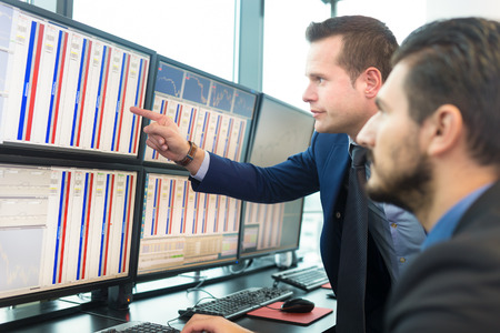 trader: Businessmen trading stocks. Stock traders looking at graphs, indexes and numbers on multiple computer screens. Colleagues in discussion in traders office.