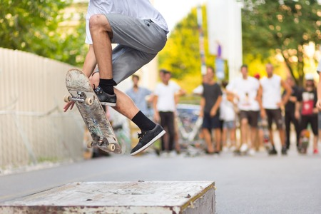 skateboard shoes: Young skateboarder skateboarding on an object in street. Skateboarding legs doing trick ollie at skatepark. Group of friends cheering in the background.