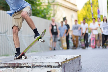 skateboard shoes: Young skateboarder skateboarding on the street. Skateboarding legs doing slide trick on object. Group of friends cheering in the background. Stock Photo