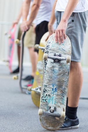 street life: Young skateboarders skateboarding on the street. Group of friends standing in a row with skateboards in their hands. Urban life. Youth subculture. Stock Photo