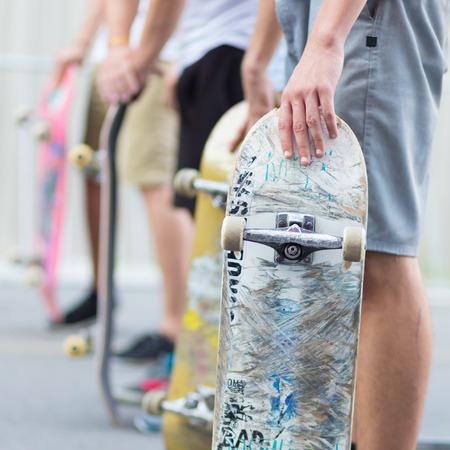 juventud: Patinadores jóvenes que andan en monopatín en la calle. Grupo de amigos de pie en una fila con los monopatines en sus manos. Vida urbana. Subcultura juvenil. Foto de archivo