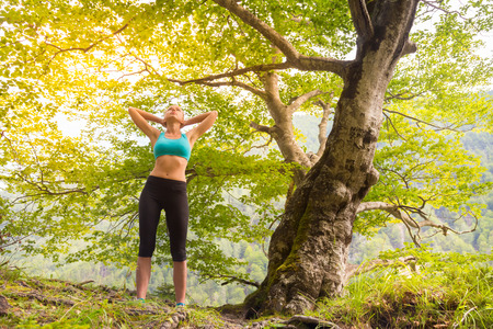 lifestile: Active sporty girl raising arms, feeling  relaxed and free in beautiful natural environment. . Concept of natural, active, healthy, lifestile.