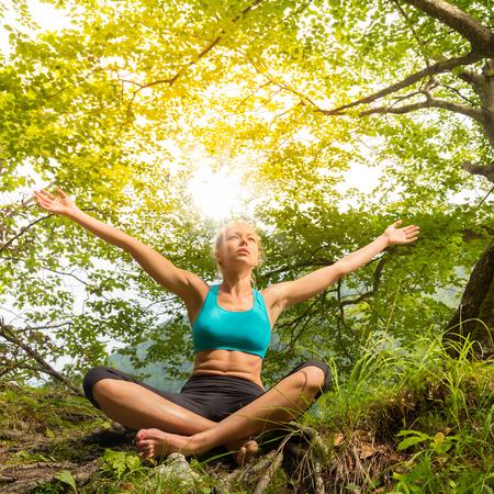 Mujer relajada disfrutando de la libertad y de la vida en el bello entorno natural. Chica dichoso levantar los brazos, sintiéndose libre, relajado y feliz. Concepto de la libertad, la felicidad, el disfrute y el equilibrio natural.