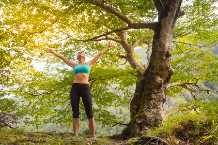 inhaling: Active sporty girl raising arms inhaling fresh air, feeling  relaxed and free in beautiful natural environment. . Concept of natural, active, healthy, lifestile.