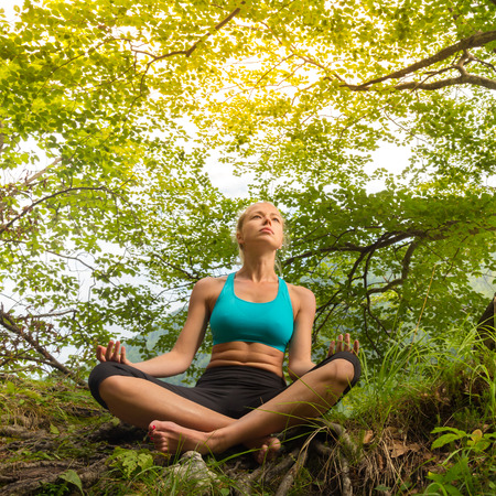 blissful: Relaxed woman enjoying freedom and life in beautiful natural environment. Blissful girl in lotus pose feeling relaxed, free and happy. Concept of freedom, happiness, enjoyment and natural balance. Stock Photo