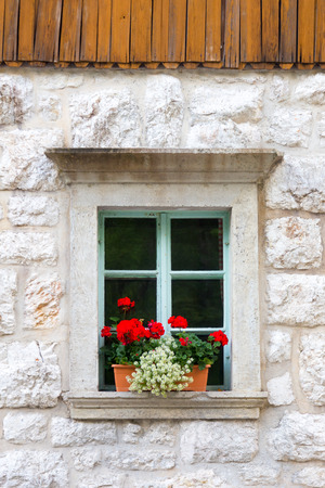vintagel: Vintagel alpine stone window with typical red carnation flowers on window sill. Stock Photo