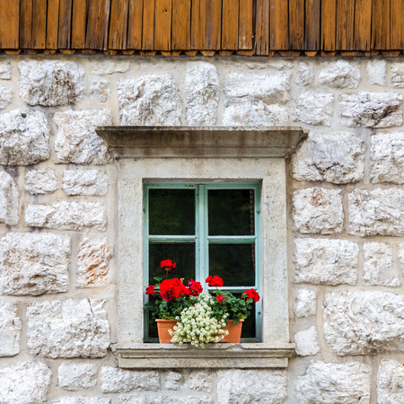 vintagel: Vintagel alpine stone window with typical red carnation flowers on window sill. Detail from traditional mountain house with wooden paneling. Stock Photo