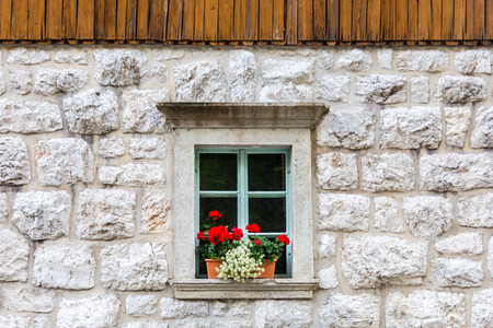 lodge: Vintagel alpine stone window with typical red carnation flowers on window sill. Detail from traditional mountain house with wooden paneling. Stock Photo