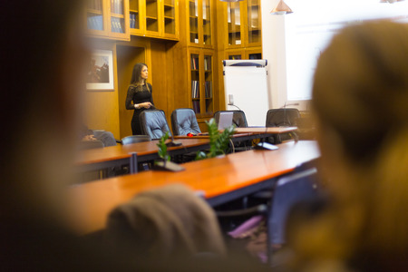 thesis: Speaker giving presentation in lecture hall at university. Female PhD candidate defending her doctoral thesis in front of the committee. Participants listening to presentation.