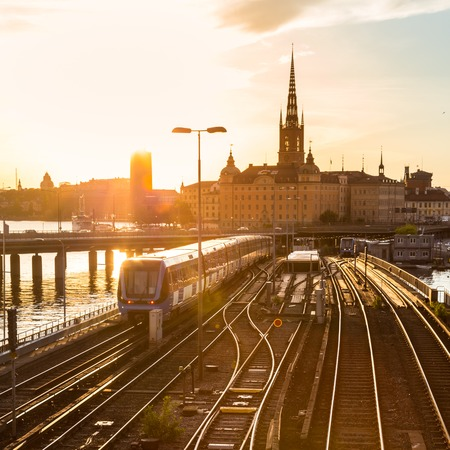 station: Railway tracks and trains near Stockholms main train station in Norrmalm area, Stockholm, Sweden in sunset.