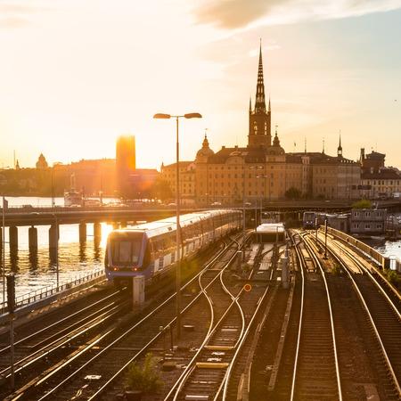 tren: Vías de ferrocarril y trenes cerca de la estación principal de trenes de Estocolmo, en el área de Norrmalm, Estocolmo, Suecia, en la puesta de sol. Foto de archivo