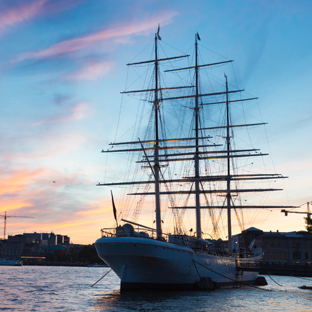gamla stan: Panoramic view of swedish capital Stockholm in sunset. Silhouette of large traditional wooden sailboat and old medieval downtown of Gamla stan in the background. Copy space. Square composition. Stock Photo