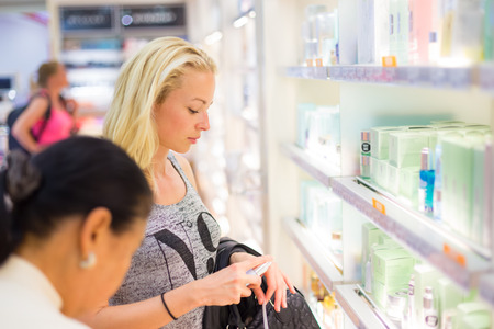 store: Casual blond young woman smelling perfume in retail store. Beautiful blond lady testing  and buying cosmetics in a beauty store.