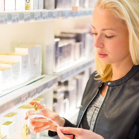 boutique: Casual blond young woman smelling perfume in retail store. Beautiful blond lady testing  and buying cosmetics in a beauty store.