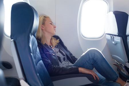 medios de transporte: Cansado señora rubia caucásico durmiendo la siesta en el asiento incómodo durante el viaje en avión. El transporte comercial por aviones. Foto de archivo