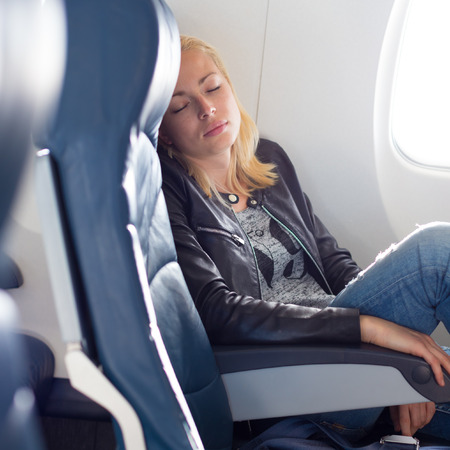 uncomfortable: Tired blonde casual caucasian lady napping on uncomfortable seat while traveling by airplane. Commercial transportation by planes.