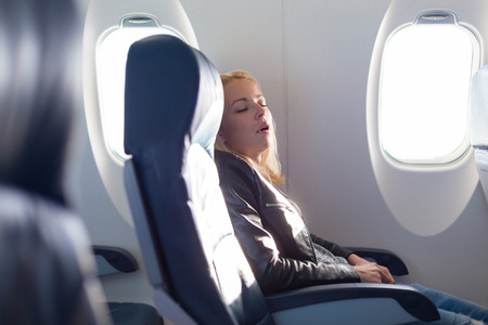 plane window: Tired blonde casual caucasian lady napping on uncomfortable seat while traveling by airplane. Commercial transportation by planes.