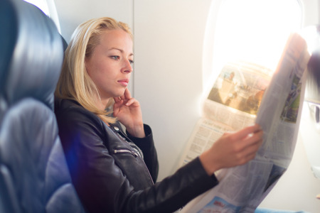 Woman reading newspaper on airplane. Female traveler reading seated in passanger cabin. Sun shining trough airplane window.