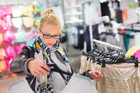 woman clothes: Woman shopping clothes. Shopper looking at clothing indoors in store. Beautiful blonde caucasian female model wearing black glasses, casual black leather jacket an colorful scarf. Stock Photo