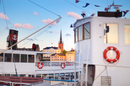 gamla stan: Swedish capital Stockholm in sunset. White traditional wooden  ferry steamer and old medieval downtown of Gamla stan in the background. Focus on background. Horisontal composition. Stock Photo