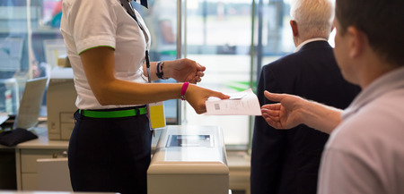 Passenger handing over air ticket at airline check in counter. Archivio Fotografico