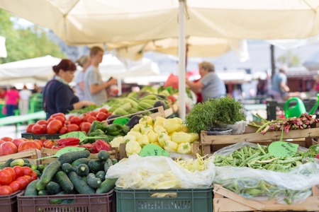 Farmers' food market stall with variety of organic vegetable. Vendor serving and chating with customers. Stock Photo