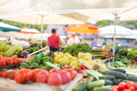 Farmers' food market stall with variety of organic vegetable. Vendor serving and chating with customers. Stockfoto