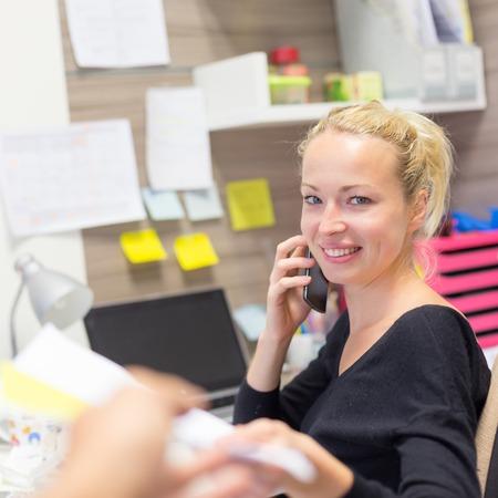 Unternehmen und Unternehmertum consept. Schöne blonde Geschäftsfrau auf dem Handy in der bunten modernen, kreativen Arbeitsumfeld zu akzeptieren Papiere sprechen. Weibliche Multi-Tasking.