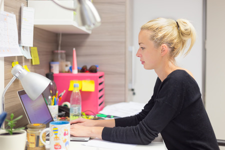 work: Business and entrepreneurship consept. Beautiful blonde business woman working on laptop in colorful modern creative working environment. Stock Photo