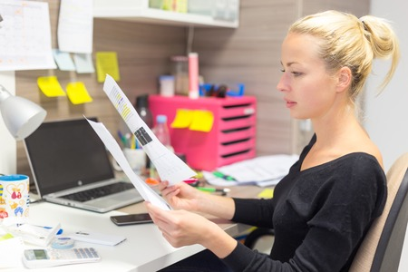 Business and entrepreneurship consept. Beautiful blonde business woman working in colorful modern creative working environment reviewing some papers. Standard-Bild