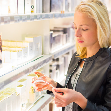 Casual blond young woman smelling perfume in retail store. Beautiful blond lady testing  and buying cosmetics in a beauty store.