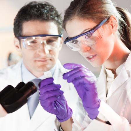 microscopio: Científico vida investigando en el laboratorio. Científico joven atractivo y su supervisor de post doctorado mirando el portaobjetos de un microscopio en el laboratorio forense. Salud y biotecnología. Foto de archivo