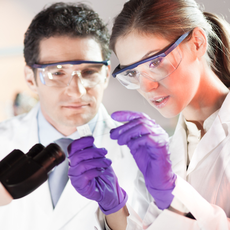 scientist man: Life scientist researching in laboratory. Attractive young scientist and her post doctoral supervisor looking at the microscope slide in the forensic laboratory. Healthcare and biotechnology.
