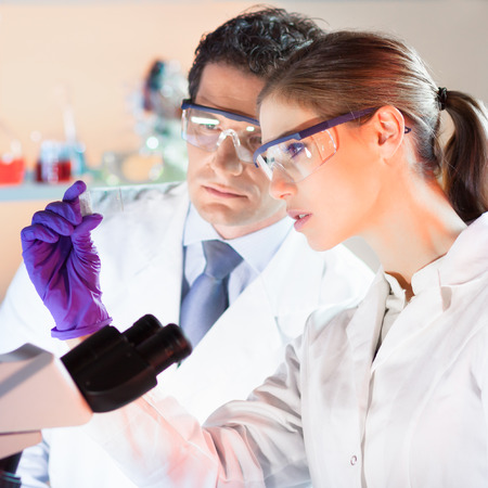 doctoral: Life scientist researching in laboratory. Attractive young scientist and her post doctoral supervisor looking at the microscope slide in the forensic laboratory. Healthcare and biotechnology.