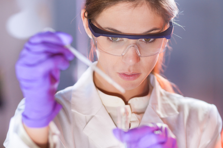 researchers: Life scientists researching in laboratory. Focused female life science professional pipetting solution into the glass cuvette. Lens focus on researchers eyes. Healthcare and biotechnology concept. Stock Photo