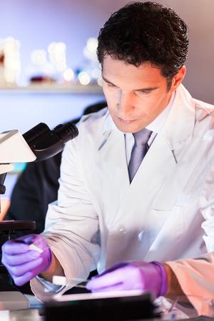 laboratorio dental: Científico vida investigando en el laboratorio. Científico masculino joven atractivo que mira en el microscopio se desliza en el laboratorio. Salud y concepto de la biotecnología.