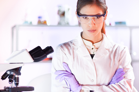 health care professional: Portrait of a attractive, young, confident female health care professional with microscope in hes working environment. Healthcare and biotechnology.