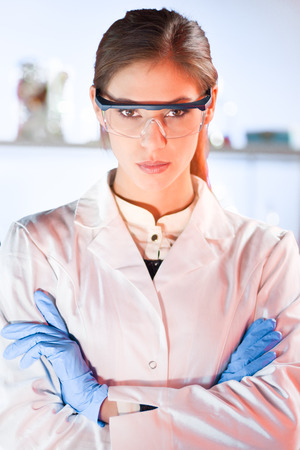 health professional: Portrait of a attractive, young, confident female health care professional in hes working environment. Healthcare and biotechnology concept.