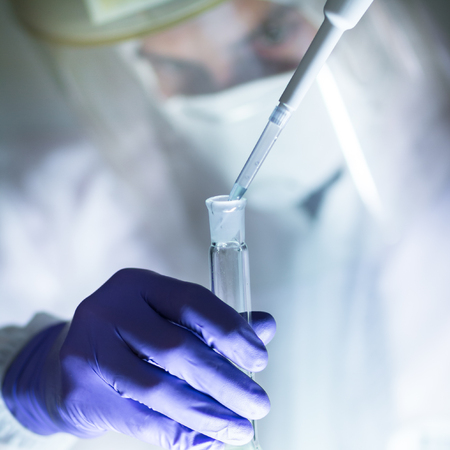 discovery: Life scientist researching in laboratory. Focused life science professional pipetting human serum media containing HIV infected cells. High protection degree work. Healthcare and biotechnology. Stock Photo